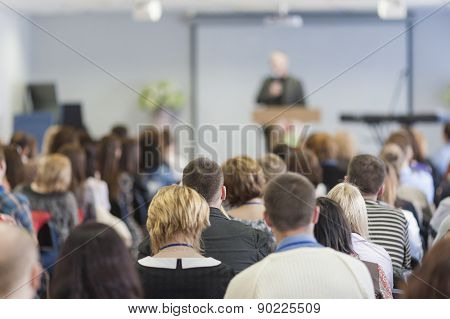 Lecturer Speaking In Front Of The Large Group Of People