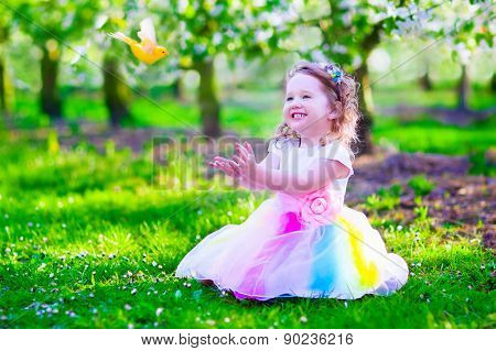 Little Girl In Fairy Costume Feeding A Bird