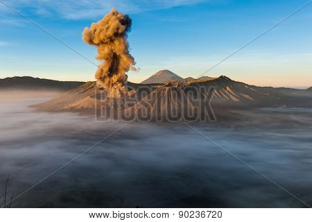JAVA, INDONESIA - JULY 2, 2011: Mount Bromo erupts spewing out ash and smoke in the misty morning. Indonesia sits on the 'ring of fire' with many active volcanoes and prone to earthquakes.