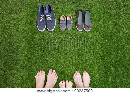 Family legs  standing  opposite shoes on  grass