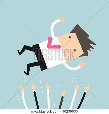 Successful businessman being throwing up in the air