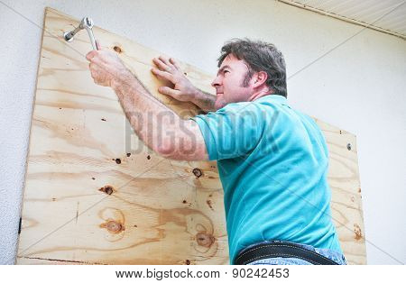 Man boarding up the windows on his home to prepare for a hurricane or tornado.