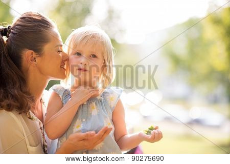 Mother Whispering To Her Daughter In The Sunshine In A City Park