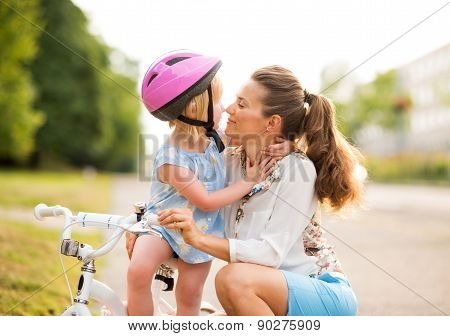 Blonde Girl In Pink Helmet Gives Eskimo Kisses To Her Mother
