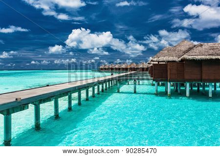Overwater villas on the tropical lagoon connected to island by jetty poster