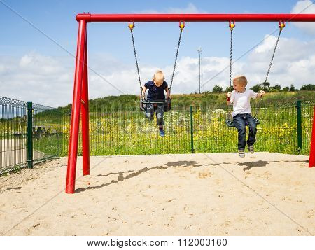 Children Boys Playing On Swing Outdoor.
