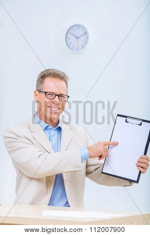 Smiling businessman showing his records.