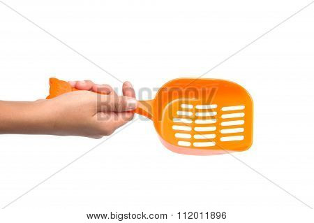 Hand with plastic scoop for cleaning cat litter