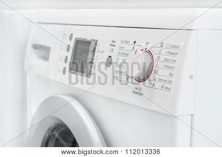 closeup of new white laundry or washing machine, selective focus on control elements