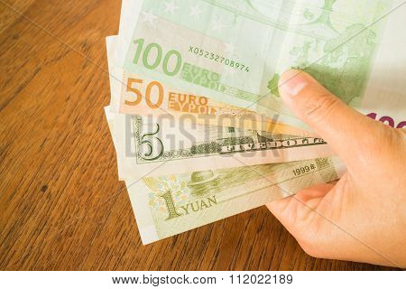 Hand On Nternational Currencies Bank Note On Wooden Table