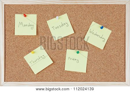 Yellow sticky Notes With Weekdays Sticked On Corkboard