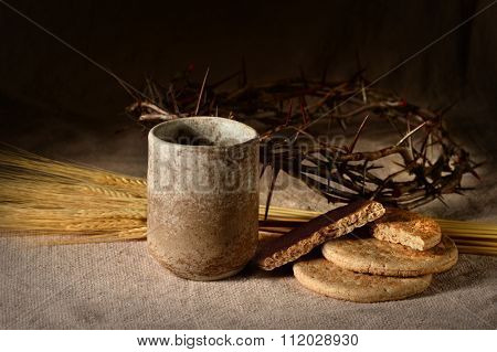 Communion elements with crown of thorns and wheat on table