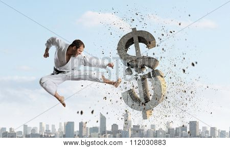 Young determined karate man breaking with leg concrete dollar sign