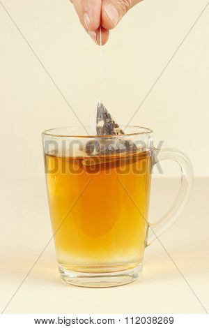 Hand brews pyramid tea bag in glass of hot water