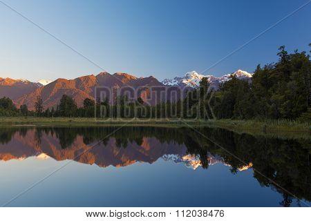 Twin Peaks Reflect In The Beautiful Lake Matheson At Sunset, New Zealand