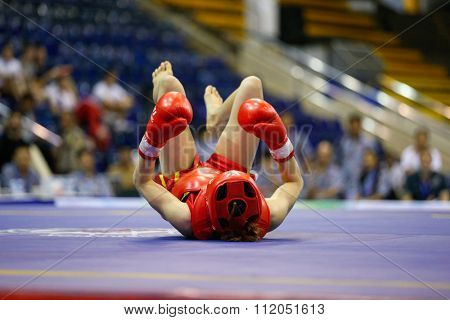 JAKARTA, INDONESIA - NOVEMBER 18, 2015: Luan Thi Hoang of Vietnam (red) fights Divine Wally of Philippines (black) in the women's 48kg Sanda finals at the 13th World Wushu Championship 2015 in Jakarta