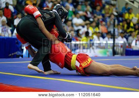 JAKARTA, INDONESIA - NOVEMBER 18, 2015: Moria Manalu of Indonesia (red) fights Sedigheh Dariaeivarkadeh of Iran (black) in the women's 60kg Sanda finals at the 13th World Wushu Championship 2015.