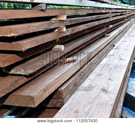 Many Unplaned Thick Planks Covered With Antiseptic Preparation