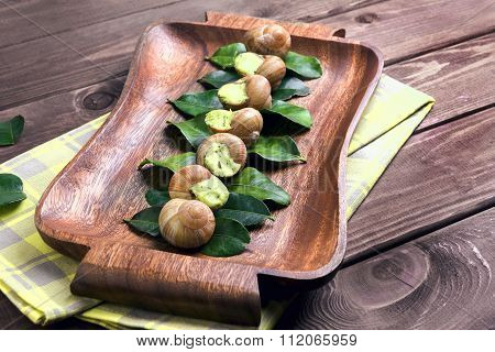 Burgundy Snail On A Wooden Tray