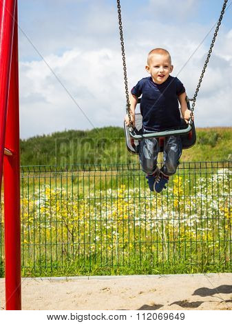 Child Boy Playing On Swing Outdoor.