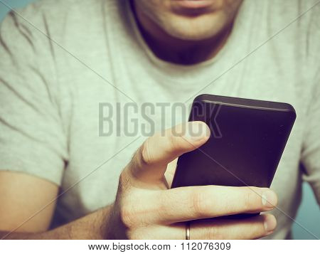 Young Caucasian Man In A Gray T-shirt Smartphone