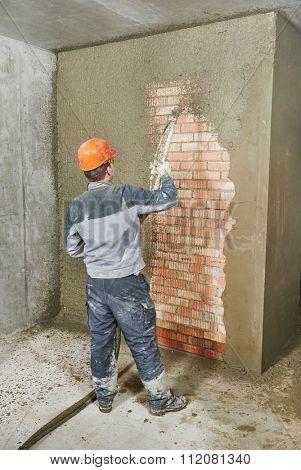Plasterer operating sprayer equipment machine for spraying thin-layer putty plaster finishing on brick wall