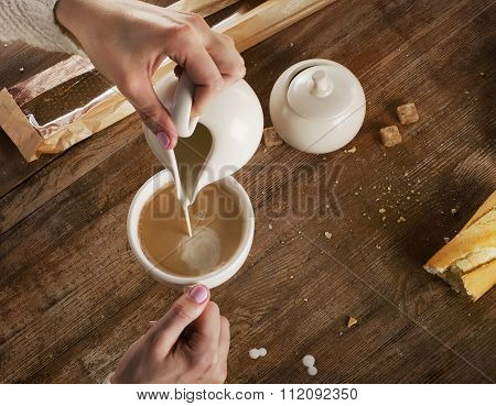 Woman Pouring Milk To Cup Of Espresso Coffee.