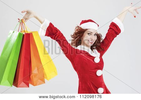 Exclaiming And Happy Caucasian Santa Girl With Many Colorful Shopping Bags. Posing Against White Bac