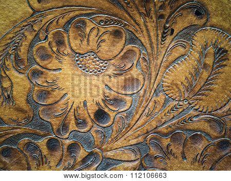 Old brown leatherwork carved detail on saddle.