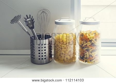 Food in glass jars on natural stone countertop.