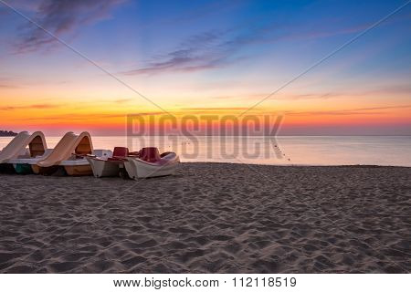 Calm Sunrise At Sea Beach With Boats