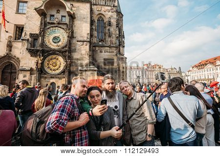 Group of tourists taking pictures against background of sights -
