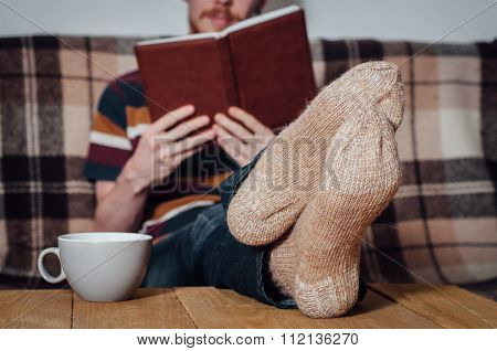 Young Man Reading Book On Coach In Holey Socks