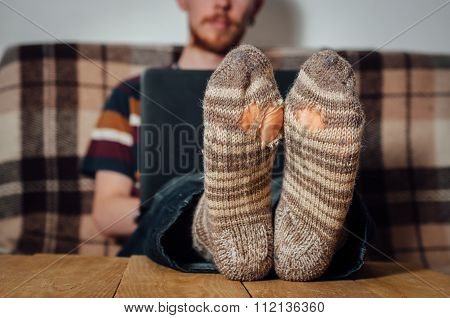 Young Man Working With Laptop In Holey Socks