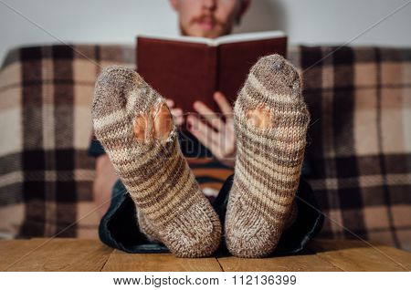 Young Man Reading Book On Couch In Holey Socks