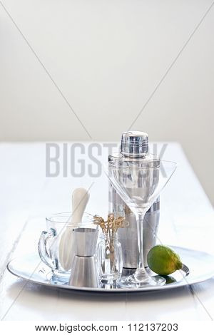 Silver tray with martini glass with cocktail making utensils accessories equipment shaker thimble measurer and lime garnish