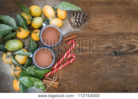 Christmas or New Year frame. Fresh mandarins with leaves, cinnamon sticks, pine cone, hot chocolate