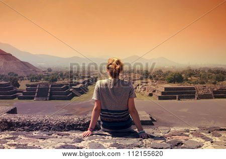 Young Female Sitting On Top Of Pyramid And Overlooking Teotihuacan Ruins