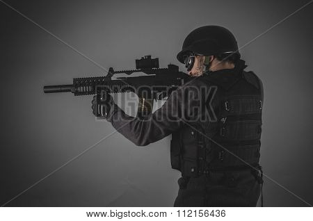 shooting, airsoft player with gun, helmet and bulletproof vest on gray background