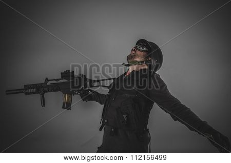 war airsoft player with gun, helmet and bulletproof vest on gray background