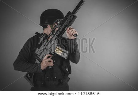 gunpowder, airsoft player with gun, helmet and bulletproof vest on gray background