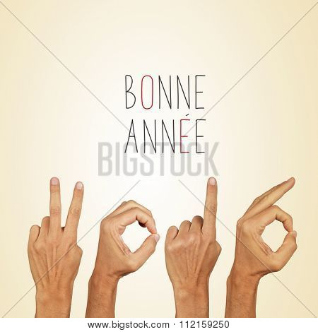 man hands forming the number 2016, as the new year, and the text bonne annee, happy new year in french, on a beige background