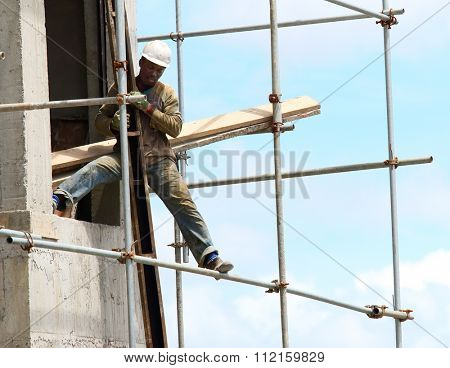 CUREPIPE, MAURITIUS ISLAND - 28. OCTOBER, 2015: Unidentified African worker on a scaffold build new touristic resort on the Mauritius coast.