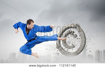 Young determined karate man breaking with leg concrete copyright sign