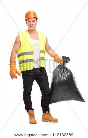 Full length portrait of a young male waste collector holding a garbage bag and looking at the camera isolated on white background