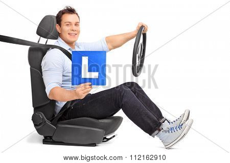 Young man holding a steering wheel and an L-sign seated on a car seat isolated on white background