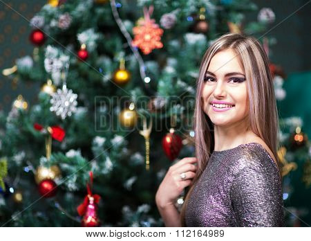 Beautiful Woman Posing In Front Of Christmass Tree