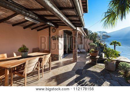 veranda of a classic house at sunset, wood furniture