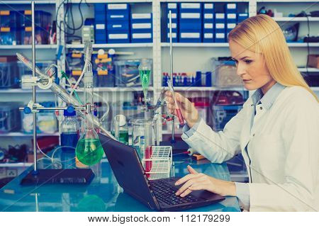 Chemical laboratory scene: attractive young student scientist observing the blue indicator color shift after the solution destillation.