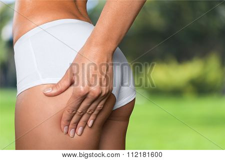 Attractive woman with perfect body checking cellulite on her buttocks, cropped image